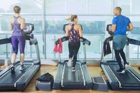 Drei Personen joggen auf Laufband in Fitnessstudio