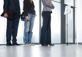 Drei Personen stehen an Schalter an, Detail Beine
