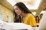 dunkelhäutige Frau mit Rastazöpfen lernt, liest in Buch