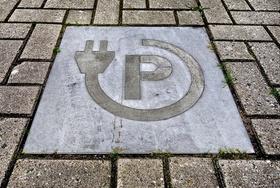 E-Ladesäule Icon in Pflastersteinen auf Parkplatz eingelegt