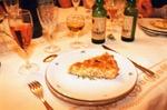 Ein Stück Quiche auf einem Teller mit Gläsern und Flaschen im Hintergrund