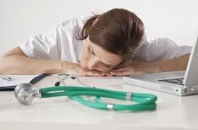 Eine müde Ärztin vor ihrem Computer