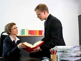 Eine Steuerberaterin und ein Steuerberater befinden sich in einer Besprechung im Büro am Schreibtisc