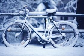 Eingeschneites Fahrrad lehnt an einem Geländer