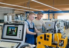 Zwei Facharbeiter bedienen eine Maschine