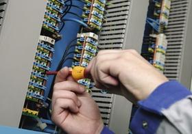 Elektriker mit Schraubenzieher an Schaltkasten, Detail Haende