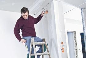 Elektriker steht auf Leiter