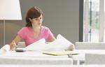 Erwachsene Frau am Schreibtisch mit Block und Rechner