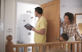 Familie schaut in Heizungsraum und Vater kontrolliert Heizung mithilfe eines Tablets
