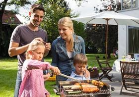 Familie ist im Garten beim Grillen
