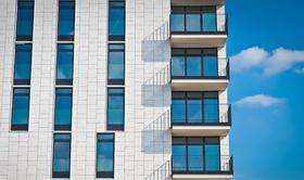 Fassade neutral mit Eckbalkonen vor blauem Himmel