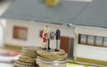 Figuren Paar und Makler auf Stapel aus Euro-Münzen vor Haus