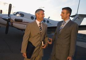 Zwei Maenner vor Geschaeftsreiseflugzeug
