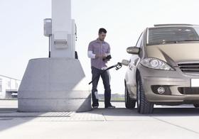 Mann mit Auto an Tankstelle, zaehlt Geld