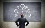 Mann schaut auf Tafel mit Fragezeichen