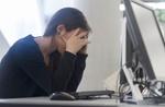 Frau am Arbeitsplatz lässt Kopf in Hände sinken