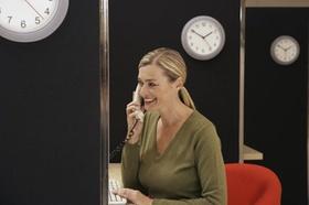 Frau am Telefon mit Uhr