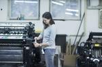 Frau an Druckmaschine in Druckerei