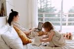 Frau arbeitet am Laptop im Bett während Tochter spielt