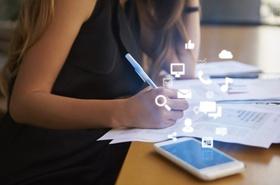 Frau arbeitet an Schreibtisch mit iPhone und App-Icons