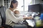 Frau arbeitet mit Baby im HomeOffice