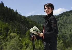 Frau beim Wandern, mit Landkarte