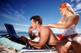 Frau cremt Mann am Strand ein