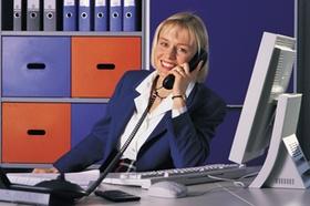 Frau die am Schreibtisch sitzt und telefoniert