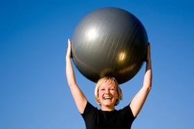 Frau, die Pezzi-Ball über dem Kopf hält