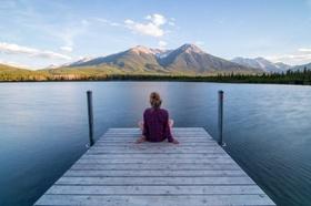 Frau entspannt an See mit Blick auf die Berge