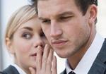Frau fluestert Mann ins Ohr