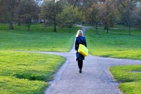 Frau geht in Park auf eine Wegkreuzung zu