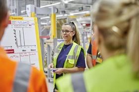 Frau gibt in Fabrikhalle Anweisungen an Team