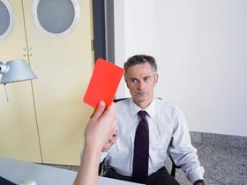 Frau hält rote Karte in der Hand und zeigt sie Mann
