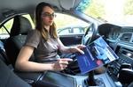 Frau im Auto sitzend hält Fahrtenbuch in der Hand