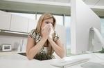 Frau im Büro putzt sich die Nase