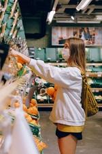 Frau kauft mit Mundschutz Orangen