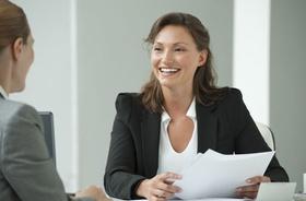 Frau lächelnd bei Bewerbungsgespräch