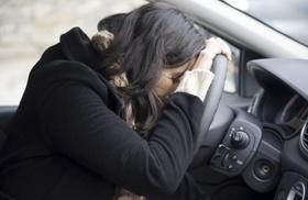 Frau lässt Kopf auf Lenkrad sinken