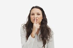 Frau legt Finger auf den Mund - schweigen