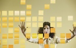 Frau lehnt Hände gegen Glaswand mit Post its