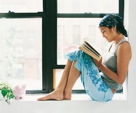 Frau liest ein Buch am Fenster