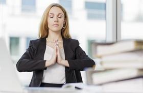 Frau macht am Arbeitsplatz Entspannungsübungen