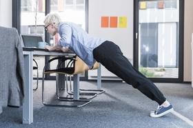 Frau macht Liegestützen am Schreibtisch