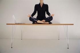 Frau macht Yoga-Übung auf Schreibtisch
