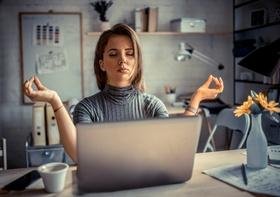 Frau macht Yoga vor Laptop
