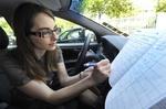Frau mit Brille sitzt im Auto und schreibt Fahrtenbuch