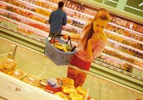 Frau mit Einkaufskorb im Supermarkt an Kuehltheke