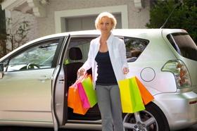 Frau mit Einkaufstaschen am Auto
