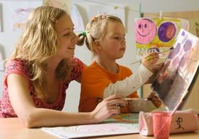 Frau mit Mädchen beim Malen mit Wasserfarben